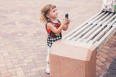 Маленькая девочка смотря мобильный телефон Стоковые Фото