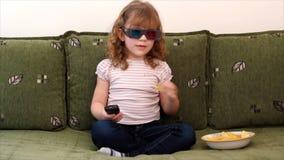 Маленькая девочка смотря ТВ видеоматериал