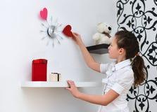 Маленькая девочка смотря часы на стене Стоковое Изображение