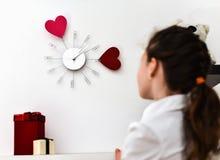 Маленькая девочка смотря часы на стене Стоковое фото RF