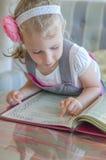 Маленькая девочка смотря через меню Стоковое фото RF