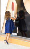 Маленькая девочка смотря через окно магазина Стоковые Изображения