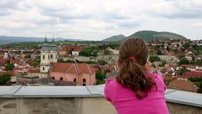 Маленькая девочка смотря через sightseeing бинокли на старом городке Eger сток-видео