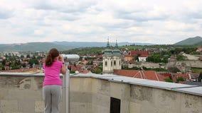 Маленькая девочка смотря через sightseeing бинокли на Eger видеоматериал