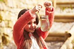 Маленькая девочка смотря Frogspawn в опарнике стоковая фотография
