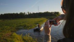 Маленькая девочка снимая ее rowing друга на шлюпке Каникулы летнего времени на озере Отснятый видеоматериал образа жизни HD Slowm сток-видео