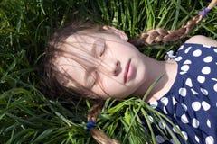 Маленькая девочка спать на зеленой траве стоковые фотографии rf