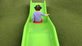 Маленькая девочка сползает вниз на скольжение в спортивной площадке сток-видео