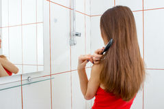 Маленькая девочка стоит близко зеркало и расчесывать их длинный гребень волос Стоковое Фото