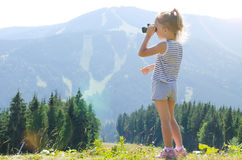 Маленькая девочка стоит на верхней части горы и смотрит до конца Стоковое Изображение
