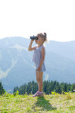 Маленькая девочка стоит на верхней части горы и смотрит до конца Стоковые Изображения