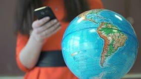 Маленькая девочка стоит перед глобусом мира сток-видео