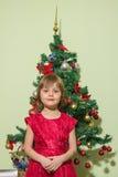 Маленькая девочка стоит перед рождественской елкой Стоковая Фотография RF
