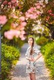 Маленькая девочка стоя близко дерево с цветками Стоковые Фотографии RF