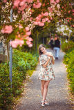 Маленькая девочка стоя близко дерево с цветками Стоковая Фотография