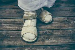 Маленькая девочка стоя деревянная предпосылка пола Крупный план ног Стоковое фото RF