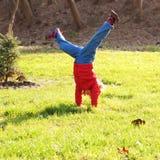 Маленькая девочка стоя на руках вверх ногами стоковое фото rf