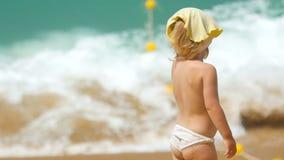 Маленькая девочка стоя против океанских волн видеоматериал
