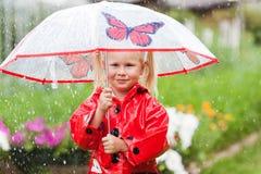 Маленькая девочка счастливой потехи милая в красном плаще с зонтиком идя в лето парка Стоковые Фото