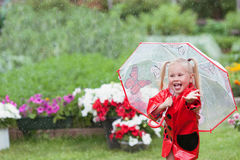 Маленькая девочка счастливой потехи милая в красном плаще с зонтиком идя в лето парка Стоковое Изображение