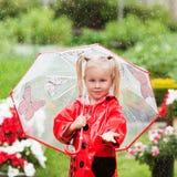 Маленькая девочка счастливой потехи милая в красном плаще с зонтиком идя в лето парка Стоковые Изображения RF