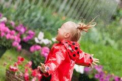 Маленькая девочка счастливой потехи милая в красном плаще с зонтиком идя в лето парка Стоковые Изображения