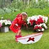 Маленькая девочка счастливой потехи милая в красном плаще с зонтиком идя в лето парка Стоковое Изображение RF
