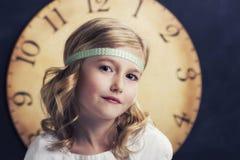 Маленькая девочка с большими винтажными часами стоковая фотография