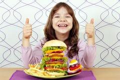 Маленькая девочка с большими гамбургером и большими пальцами руки вверх стоковые изображения rf