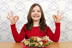 Маленькая девочка с буррито и одобренным знаком руки стоковые фото