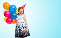 Маленькая девочка с воздушными шарами на голубой предпосылке Стоковая Фотография RF