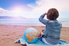 Маленькая девочка с глобусом на пляже смотря заход солнца на море Стоковое Изображение