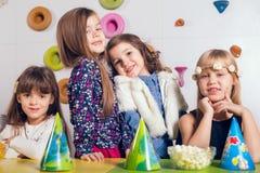 Маленькая девочка с ее друзьями на вечеринке по случаю дня рождения Стоковое Изображение RF
