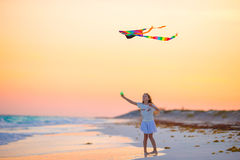 Маленькая девочка с змеем летания на тропическом пляже на заходе солнца Игра ребенк на береге океана Ребенок с игрушками пляжа Стоковое фото RF