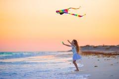 Маленькая девочка с змеем летания на тропическом пляже на заходе солнца Игра ребенк на береге океана Ребенок с игрушками пляжа Стоковые Фотографии RF