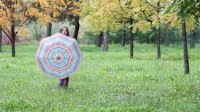 Маленькая девочка с зонтиком в парке осени сток-видео