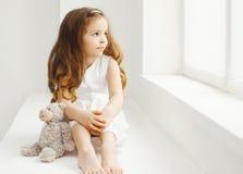 Маленькая девочка с игрушкой плюшевого медвежонка дома в белой комнате Стоковое фото RF
