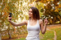 Маленькая девочка с длинными волосами в парке с мобильным телефоном Стоковое Изображение RF