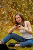Маленькая девочка с длинными волосами в парке с мобильным телефоном Стоковая Фотография RF