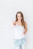 Маленькая девочка с длинными волосами усмехаясь и показывая ` жеста холодное `, оценку выставок косметического продукта, рекоменд стоковые фотографии rf