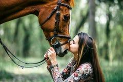 Маленькая девочка с длинными волосами целуя лошадь Стоковые Фотографии RF