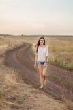 Маленькая девочка с длинными коричневыми волосами идя вдоль дороги в поле стоковая фотография rf