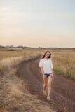 Маленькая девочка с длинными коричневыми волосами идя вдоль дороги в поле стоковая фотография
