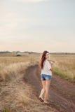 Маленькая девочка с длинными коричневыми волосами идя прочь на дорогу стоковое изображение rf