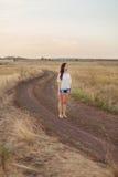 Маленькая девочка с длинными коричневыми волосами остается на дороге в поле стоковая фотография