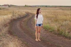 Маленькая девочка с длинными коричневыми волосами остается на дороге в поле стоковое изображение