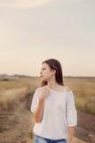 Маленькая девочка с длинными коричневыми волосами остается на дороге в поле стоковое фото rf