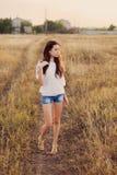 Маленькая девочка с длинным коричневым пребыванием волос на луге стоковые фото