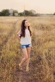 Маленькая девочка с длинным коричневым пребыванием волос на луге стоковая фотография