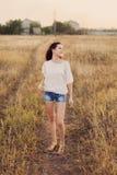 Маленькая девочка с длинным коричневым пребыванием волос на луге, усмехаясь стоковые фотографии rf